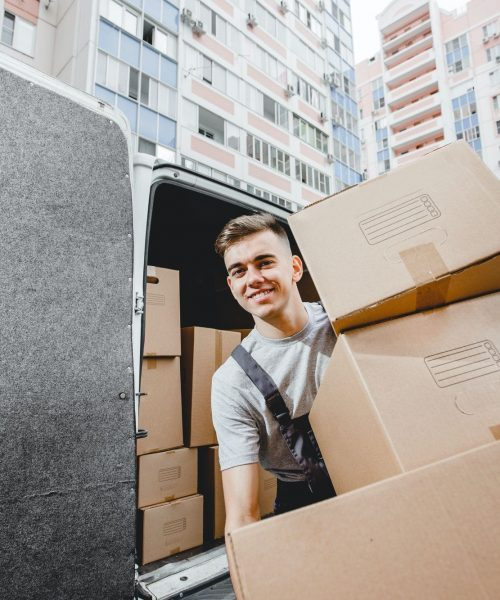A young handsome smiling worker wearing uniform is unloading the van full of boxes. The block of